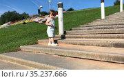 Toddler girl wearing jeans climbing on stone stairs outdoor, wide cement stairway up to hill. Стоковое видео, видеограф Кекяляйнен Андрей / Фотобанк Лори