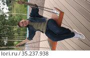 Vertical video of Caucasian woman swinging on the swings. Happy adult female enjoying on playground. Стоковое видео, видеограф Кекяляйнен Андрей / Фотобанк Лори