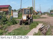 Старый трактор стоит на деревенской улице в летний солнечный день. Стоковое фото, фотограф Светлана Попова / Фотобанк Лори