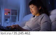 woman with laptop in bed at home at night. Стоковое видео, видеограф Syda Productions / Фотобанк Лори