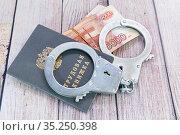 Трудовая книжка, наручники и деньги. Ответственность за нарушение трудового законодательства. Стоковое фото, фотограф Наталья Осипова / Фотобанк Лори