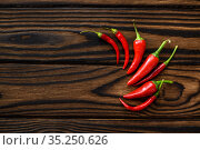 Fragrant red pepper isolated on wooden background. Стоковое фото, фотограф Tryapitsyn Sergiy / Фотобанк Лори