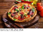 Пицца с грибами, колбасой и оливками на деревянном фоне. Стоковое фото, фотограф Марина Володько / Фотобанк Лори