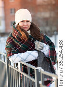 Portrait of young ttractive woman in winter clothing, red checkered scarf and woolen gloves, standing on an urban street. Стоковое фото, фотограф Кекяляйнен Андрей / Фотобанк Лори