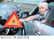 Woman a driver holding triangle sign is in her hand, sitting in car after road collision with motorcycle. Стоковое фото, фотограф Кекяляйнен Андрей / Фотобанк Лори