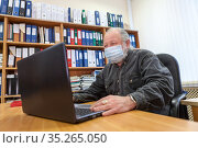 Mature man wearing facemask using laptop at work place in office, protection due Covid-19 pandemic. Стоковое фото, фотограф Кекяляйнен Андрей / Фотобанк Лори