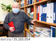 Senior male archivist holding red notebook and looking at camera, man wearing facial mask due coronavirus pandemic. Стоковое фото, фотограф Кекяляйнен Андрей / Фотобанк Лори