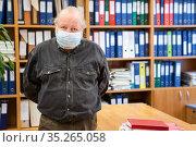 Portrait of senior male archivist with hands behind back looking at camera, man wearing facial mask due coronavirus pandemic, copyspace. Стоковое фото, фотограф Кекяляйнен Андрей / Фотобанк Лори
