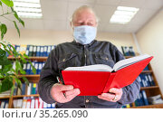 Mature male archivist holding open notebook in hands, looking at camera, man wearing face mask due Covid-19 pandemic. Focus is on red organiser. Стоковое фото, фотограф Кекяляйнен Андрей / Фотобанк Лори
