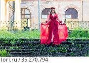 Девушка в красном платье спускається по лестнице. Стоковое фото, фотограф Литвяк Игорь / Фотобанк Лори