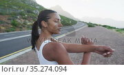 African american woman wearing sportswear performing stretching exercise on the road. Стоковое видео, агентство Wavebreak Media / Фотобанк Лори