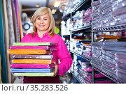 Portrait of mature woman showing stack of bedsheet in the textile shop. Стоковое фото, фотограф Яков Филимонов / Фотобанк Лори