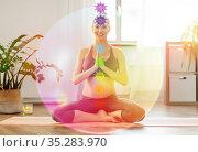 happy pregnant woman meditating with seven chakras. Стоковое фото, фотограф Syda Productions / Фотобанк Лори