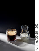 coffee in glass and jug of milk or cream on table. Стоковое фото, фотограф Syda Productions / Фотобанк Лори