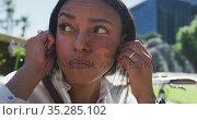 African american woman putting earphones on in city park. Стоковое видео, агентство Wavebreak Media / Фотобанк Лори