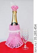 Вязаный розовый наряд шампанского с прозрачным бокалом, расписанным точечной техникой Point-to-point, на светлом фоне. Стоковое фото, фотограф Вера Смолянинова / Фотобанк Лори