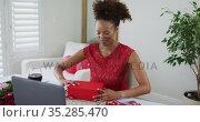 Mixed race woman on a valentines date video call, opening gift. Стоковое видео, агентство Wavebreak Media / Фотобанк Лори