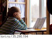 Школьница внимательно читает задание в учебнике сидя дома за столом у окна. Стоковое фото, фотограф Иванов Алексей / Фотобанк Лори