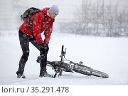 Caucasian ciclist stands on bike lane and holding his injured knee after falling down from bicycle, slippery and snowy pathway in town at winter season. Стоковое фото, фотограф Кекяляйнен Андрей / Фотобанк Лори