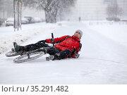 Fallen down Caucasian cyclist lying on slippery snowy pathway, riding bicycle in city at winter season. Стоковое фото, фотограф Кекяляйнен Андрей / Фотобанк Лори
