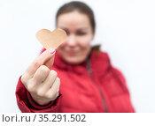 Caucasian woman stretching shape of heart made from paper, red winter jacket, white background, focus is on heart. Стоковое фото, фотограф Кекяляйнен Андрей / Фотобанк Лори