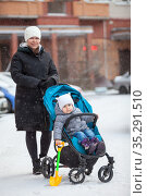 Young mother standing with her toddler child sitting in baby carriage, full-length portrait outdoor at winter time. Стоковое фото, фотограф Кекяляйнен Андрей / Фотобанк Лори