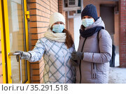 Two Caucasian women ready to enter the door of shop or store, females wearing medical mask to protect coronavirus infection. Safety rules for public place. Стоковое фото, фотограф Кекяляйнен Андрей / Фотобанк Лори