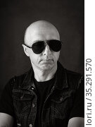 Unshaven, bald middle-aged man in a black T-shirt, denim vest and dark glasses. Black and white portrait. Photo taken in studio. Стоковое фото, фотограф Вадим Орлов / Фотобанк Лори