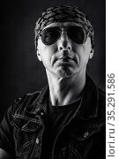 Unshaven, middle-aged man in a T-shirt, denim vest, bandana and sunglasses. Black and white portrait. Photo taken in studio. Стоковое фото, фотограф Вадим Орлов / Фотобанк Лори
