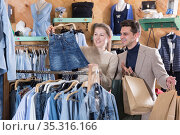 Smiling woman and man are choosing clothes and looking on jeans skirt. Стоковое фото, фотограф Яков Филимонов / Фотобанк Лори