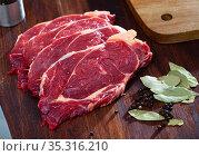 Sliced beef pieces on dark wooden board with laurel leafs and peas of bitter pepper. Стоковое фото, фотограф Яков Филимонов / Фотобанк Лори