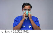 indian male doctor in mask putting on goggles. Стоковое видео, видеограф Syda Productions / Фотобанк Лори