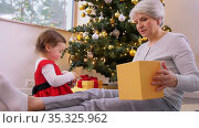 grandmother and baby with christmas gift and decor. Стоковое видео, видеограф Syda Productions / Фотобанк Лори