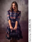 Портрет красивой девушки на сером фоне, девушка держит черную дамскую сумочку двумя руками перед собой. Стоковое фото, фотограф Иванов Алексей / Фотобанк Лори