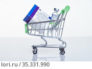 Shopping cart with Vaccine box and vial with Sputnik V vaccine Gam-COVID-Vac on white table with reflection. Редакционное фото, фотограф Serg Zastavkin / Фотобанк Лори