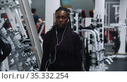 A black woman in headphones takes two dumbbells in the gym. Стоковое видео, видеограф Константин Шишкин / Фотобанк Лори
