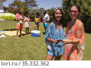 Portrait of two mixed race female friends looking at camera and smiling at a pool party. Стоковое фото, агентство Wavebreak Media / Фотобанк Лори