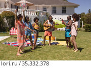 Diverse group of friends dancing and smiling at a pool party. Стоковое фото, агентство Wavebreak Media / Фотобанк Лори