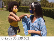 Two diverse female friends wearing face masks bumping elbows at a pool party. Стоковое фото, агентство Wavebreak Media / Фотобанк Лори