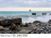 Beach with ruins of industrial structures and rickety aquaculture outpost far out to sea. Стоковое фото, фотограф Евгений Харитонов / Фотобанк Лори
