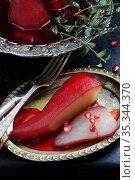Груша пашот в красном вине на черном фоне. Стоковое фото, фотограф Марина Володько / Фотобанк Лори
