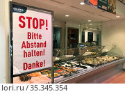 Berlin, Germany, effects of corona pandemic: request in a supermarket to keep distance between customers (2020 год). Редакционное фото, агентство Caro Photoagency / Фотобанк Лори