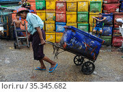 Yangon, Myanmar, worker pulling a sack truck with cooling box at the traditional Baho San Pya fish market (2014 год). Редакционное фото, агентство Caro Photoagency / Фотобанк Лори