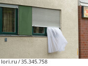 Berlin, Germany - Curtain caught in the roller shutter of a window (2019 год). Редакционное фото, агентство Caro Photoagency / Фотобанк Лори