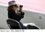 Hamburg, Germany, woman looking through her binoculars from loge 13 at racecourse. Редакционное фото, агентство Caro Photoagency / Фотобанк Лори