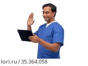 doctor or male nurse has video call on tablet pc. Стоковое фото, фотограф Syda Productions / Фотобанк Лори