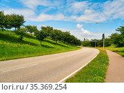 Leere Straße mit Kurve und Bürgersteig neben Hügel in einer Stadt... Стоковое фото, фотограф Zoonar.com/Robert Kneschke / age Fotostock / Фотобанк Лори