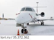 10-02-2021 KAZAN, RUSSIA, Kazan International Airport: small white airplane on the airfield in winter time. Редакционное фото, фотограф Константин Шишкин / Фотобанк Лори