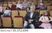 caucasian family sitting at scary premiere in theatrical hall. Стоковое видео, видеограф Яков Филимонов / Фотобанк Лори