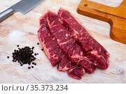 Sliced pieces of raw beef tenderloin on wooden cutting board. Стоковое фото, фотограф Яков Филимонов / Фотобанк Лори